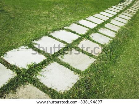 stone walkway on green grass - stock photo