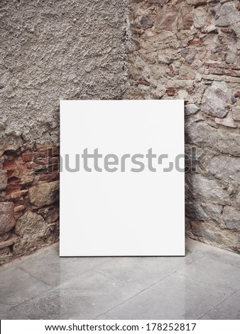 Stone wall and white poster - stock photo