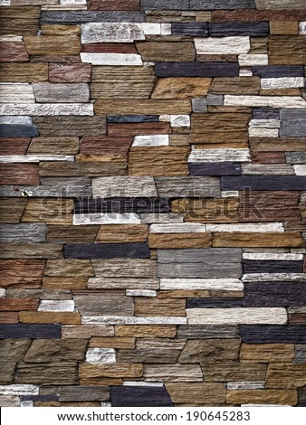 Stone wall background, pattern gray color of modern style design decorative uneven cracked real stone wall surface with cement - stock photo