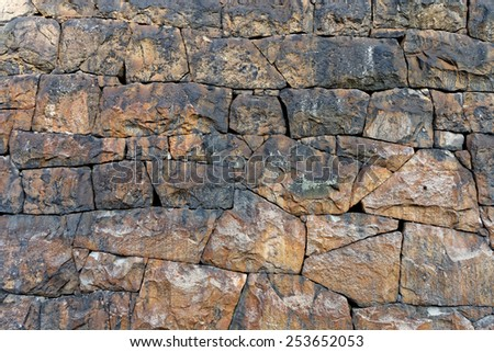 Stone wall made of irregular shaped stones in brown shades - stock photo