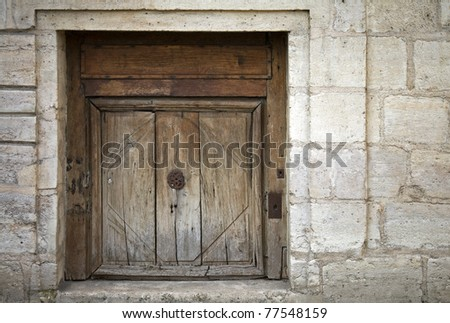 Stone wall of an ancient building with old weathered wooden gate - stock photo