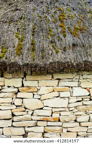 Stone wall under the moss-grown straw-thatched roof. Old Ukrainian architecture. - stock photo