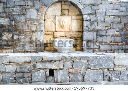 Stone wall with a water fountain and bowl set into an arched alcove of lighter colored sandstone - stock photo