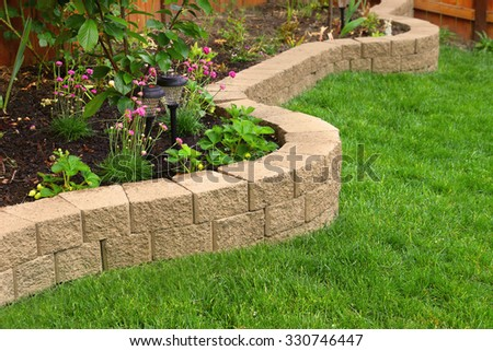 stone wall with perfect grass landscaping in garden with artificial grass - stock photo