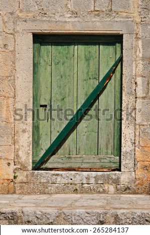 Stone wall with weathered obsolete green wooden door - stock photo