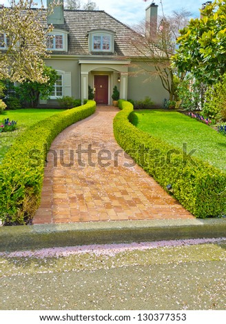 Stoned, paved house doorway, trail with nicely trimmed and landscaped bushes in front of the house entrance. - stock photo