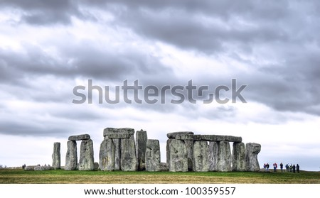 Stonehenge under a threatening sky. Distant tourists define the scale of the standing stones. - stock photo
