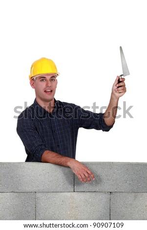 Stonemason holding up a trowel - stock photo