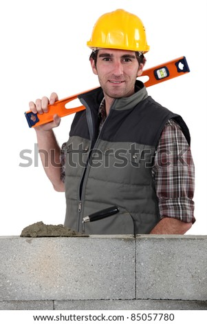 Stonemason standing before a wall and carrying a spirit level - stock photo