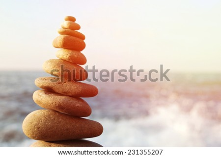 Stones balance, pebbles stack over blue sea - stock photo