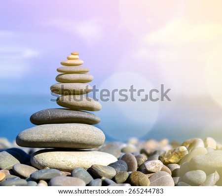 Stones balance, pebbles stack over blue sea in Crimea. Blue sky on sunny beach in summer - stock photo