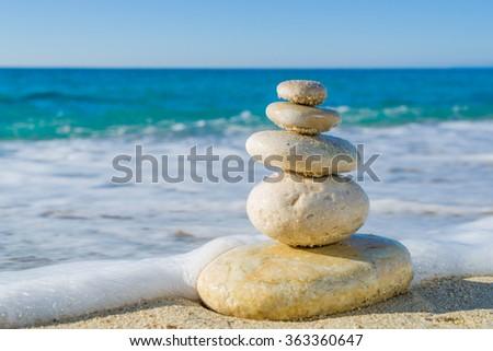 Stones balance, pebbles stack over blue sea in Croatia. Blue sky on sunny adriatic coast in summer. - stock photo