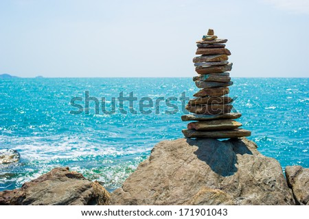Stones balance, pebbles stack over blue sea in Thailand. Blue sky on sunny in summer. - stock photo