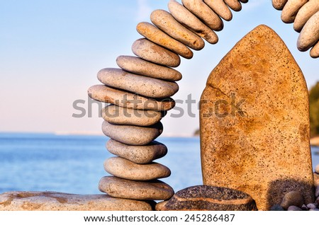 Stones laid out in the form of a arch on the sea coast  - stock photo