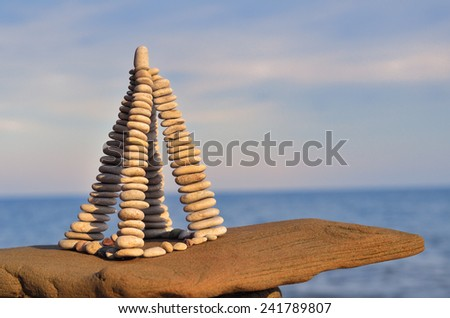 Stones laid out in the form of a pyramid on the seashore - stock photo