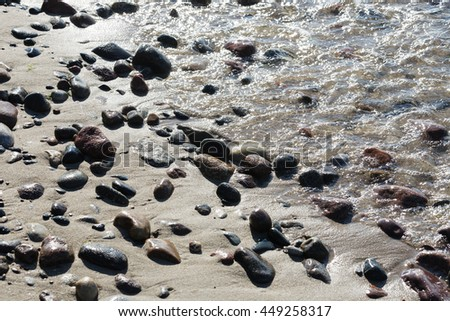 Stones on a sandy beach at the coastline of the Baltic Sea in the back light in Kolobrzeg in Poland - stock photo