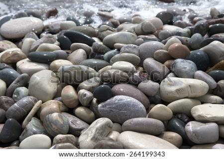 Stones on beach and sea water. - stock photo