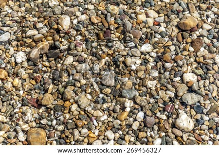 Stones on beach and sea water in bright sunset light - stock photo