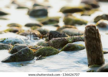 Stones on Icy Winter Beach - stock photo