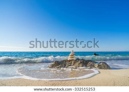 Stones pyramid on sand symbolizing zen, harmony, balance. Ocean in the background - stock photo