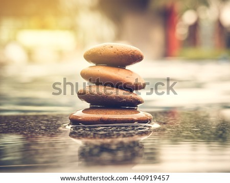 Stones pyramid with swimming pool blur background and sunlight. Photo of symbolizing zen concept and vintage style. - stock photo