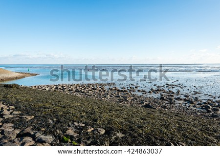 Stones, seaweed, waves and beacons at a Dutch sea loch on a sunny day. - stock photo