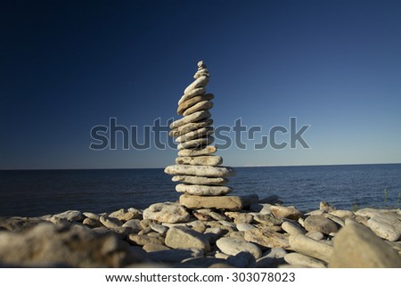 stones stacked on each other on the background of the ocean - stock photo
