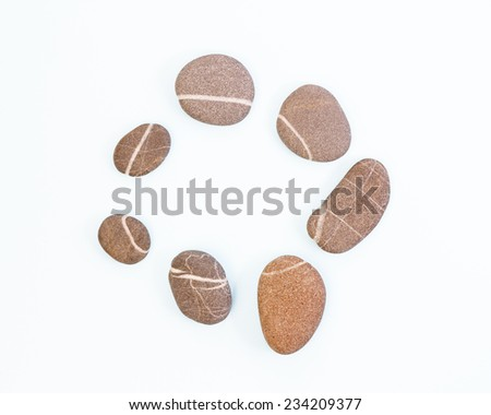 Stones with a white stripe in a circle against light blue background - stock photo
