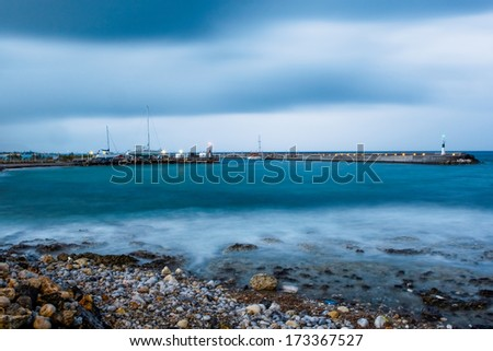 Stony shoreline littered with pebbles bordering a sheltered bay with boats moored in a harbour behind a stone pier on the horizon - stock photo