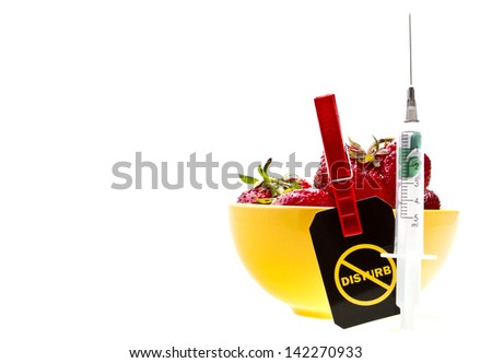 "Stop GMO concept shot. Genetic food engineering concept with a fresh red strawberry in a yellow plate, syringe with capsules and ""Do not disturb"" label on a clothespin. - stock photo"