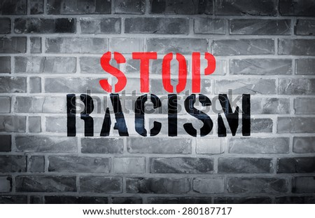 Stop racism stencil print on white wall background - stock photo