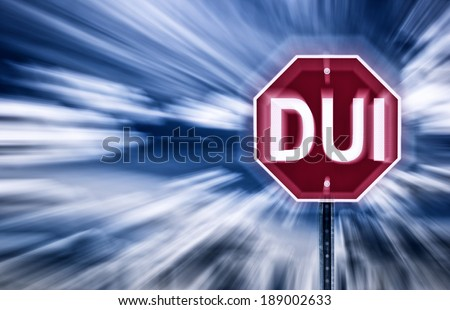 Stop sign against a moody sky with the letters DUI printed on it.  Image is blurred to imply motion and blurred vision due to intoxication.      - stock photo