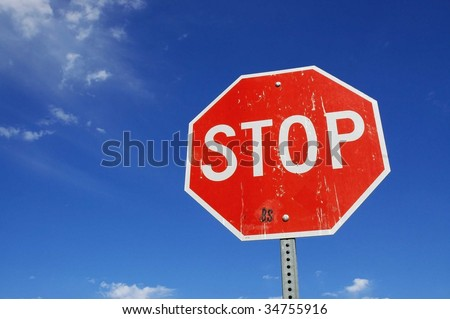 Stop sign, blue sky and wispy clouds room for copy space - stock photo