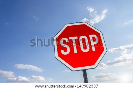 stop sign in front of a cloudy summer sky - stock photo