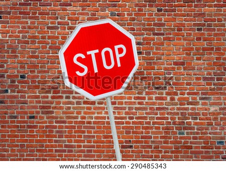 Stop sign on a brick wall background  - stock photo