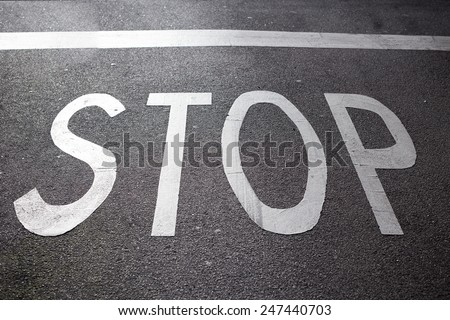 Stop sign painted on the road asphalt  - stock photo