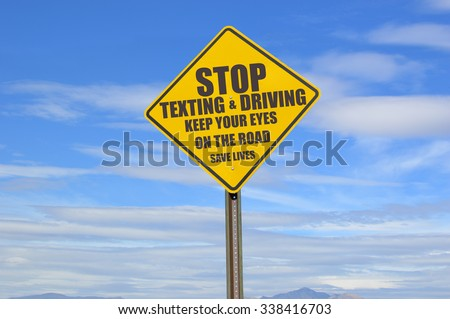 Stop Texting & Driving Keep Your Eyes on the Road Save Lives Yellow Traffic Sign blue sky clouds tips of mountains - stock photo