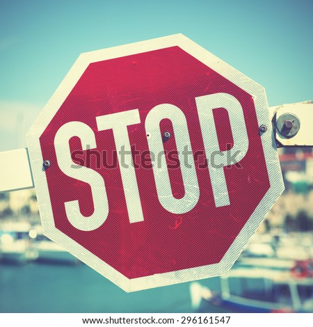 Stop traffic sign on the barrier. Retro style filtred image - stock photo