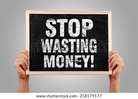 Stop Wasting Money blackboard is holden by hands with gray background. - stock photo