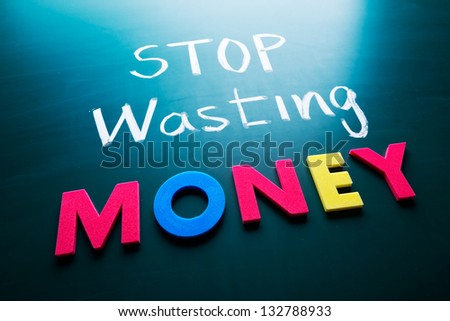 Stop wasting money concept, colorful words on blackboard - stock photo