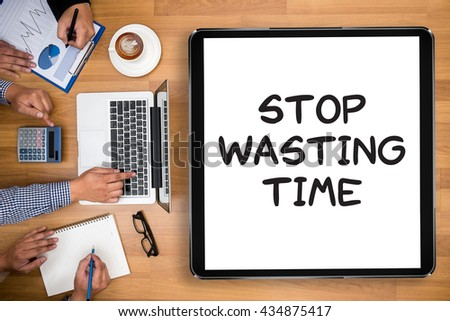 Stop Wasting Time Business team hands at work with financial reports and a laptop - stock photo