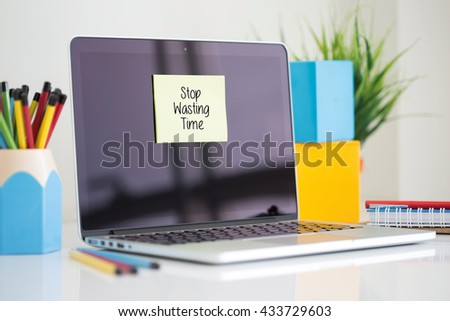 Stop Wasting Time sticky note pasted on the laptop - stock photo