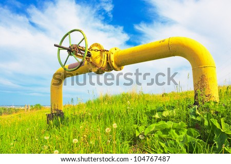 Stopcock on the pipe among grass beneath cloudy sky - stock photo