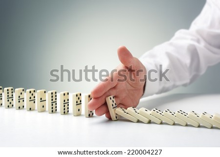 Stopping the domino effect concept for business solution, strategy and successful intervention - stock photo