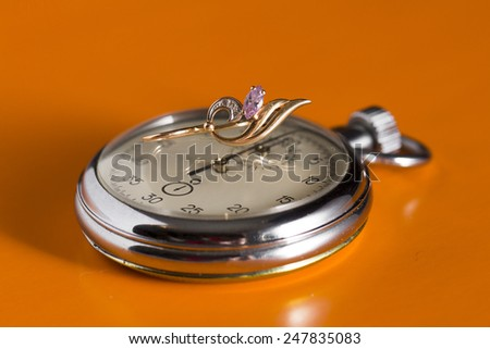 stopwatch and brooch on an orange background - stock photo