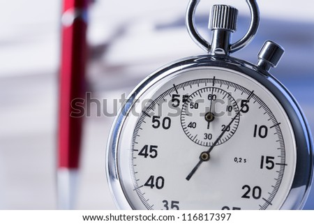 Stopwatch and pen on background of paper cards - stock photo