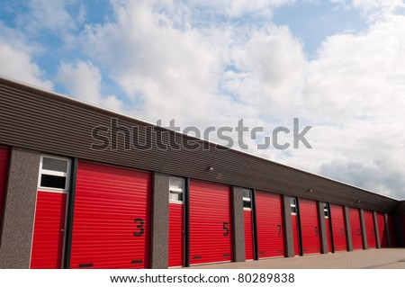 storage building with red  numbered doors - stock photo