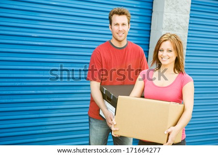 Storage: Couple Carrying Boxes To Storage Unit - stock photo