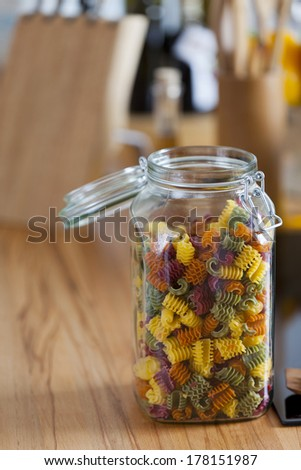 Storage Jar with Colorful Pasta and Cooking Spoon on Worktop with Copy Space in the left and upper Area of the Image - stock photo