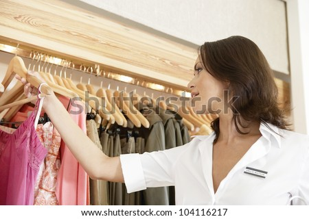 Store assistant sorting clothes on store's rails, close up. - stock photo
